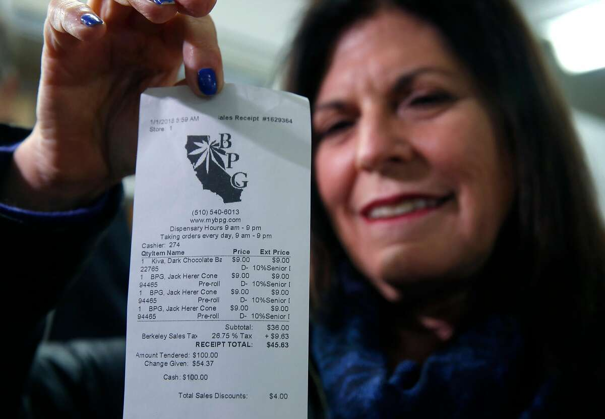 Mikki Morris holds the cash receipt for the first transaction of marijuana at the Berkeley Patients Group dispensary on the first day of legalized recreational cannabis sales in Berkeley, Calif. on Monday, Jan. 1, 2018. Morris and her husband Chris Conrad were chosen to be the first customers to buy publically at BPG.