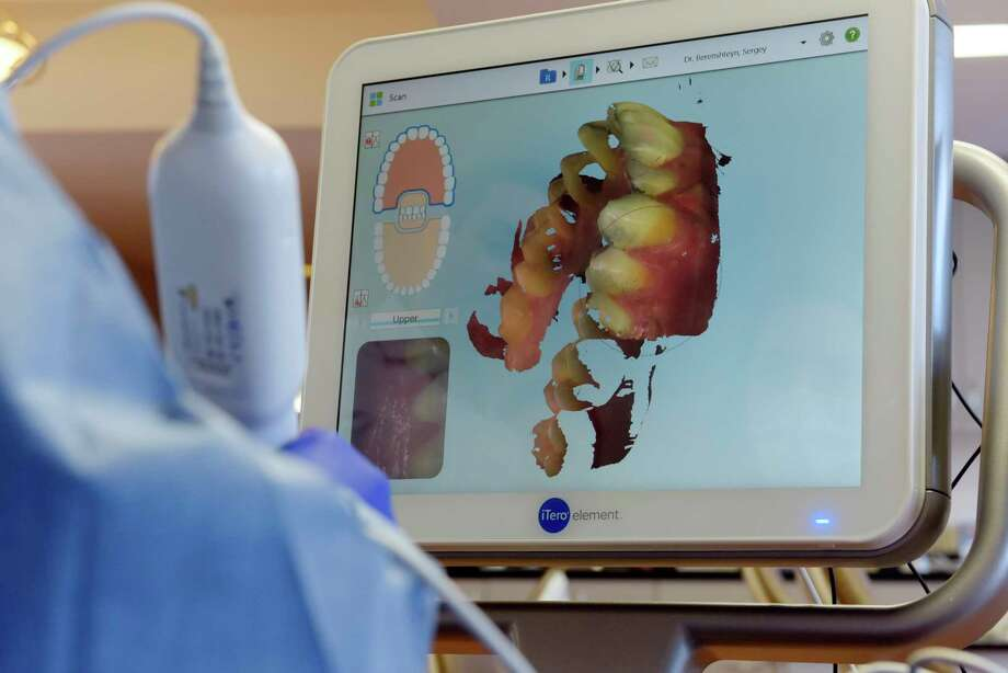 Nichole Burke, a certified dental assistant, uses a digital scanner to map out the teeth of patient, Ryan Williams, at Adirondack Orthodontics on Thursday, Dec. 14, 2017, in Guilderland, N.Y.  (Paul Buckowski / Times Union) Photo: PAUL BUCKOWSKI / 20042419A
