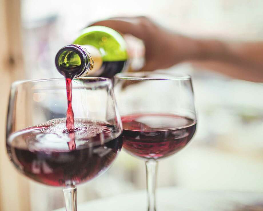 Unrecognizable man pouring red wine in two glasses. Photo: Instants, Contributor / Instants