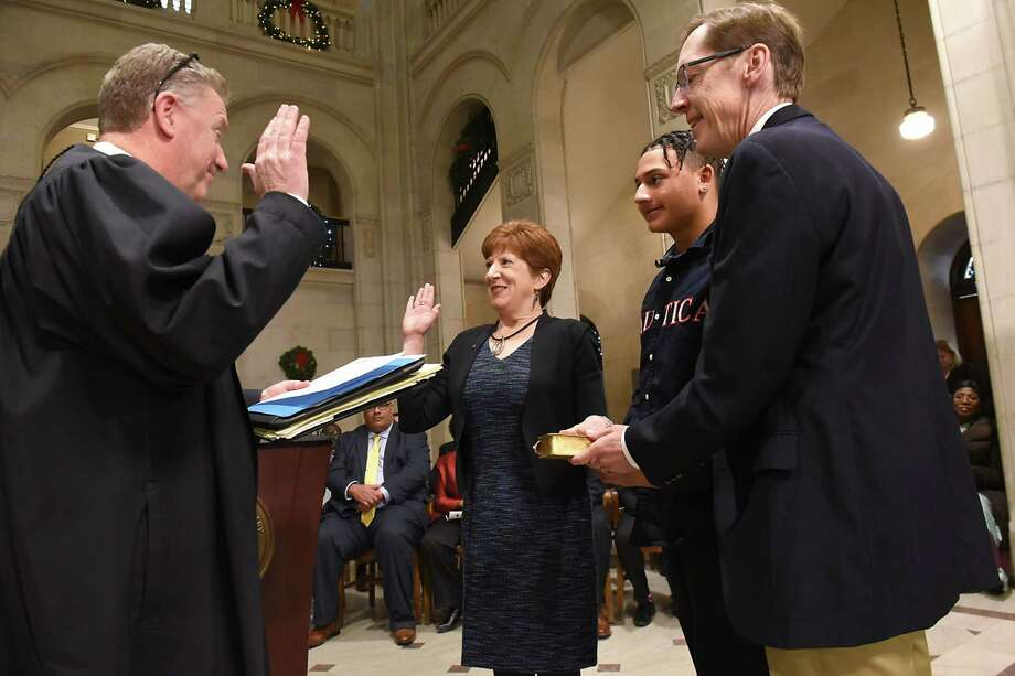 Honorable John Reilly, left, administers the oath of office to Mayor Kathy Sheehan, center, as her son Jay and husband Bob look on at City Hall on Monday, Jan. 1, 2018 in Albany, N.Y.  (Lori Van Buren / Times Union) Photo: Lori Van Buren, Albany Times Union / 20042532A