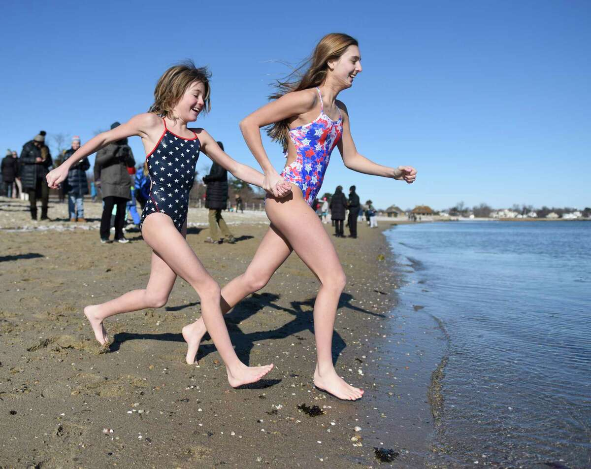 Greenwich girls Ashley Hopper, left, 11, and Lilly Hopper, 15, sprint into the water at the annual New Year's Day Dip Polar Plunge for Kids in Crisis at Greenwich Point Park in Old Greenwich, Conn. Monday, Jan. 1, 2018. Although the event was officially cancelled due to extremely cold weather, dozens of participants still plunged into the frigid waters to benefit Kids in Crisis.