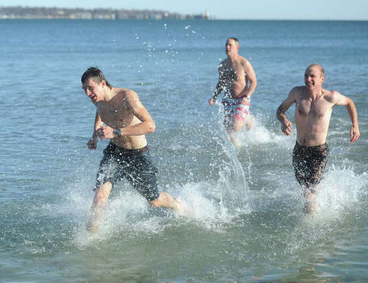 David Martinsen, left, Tom Martinsen, center, and Yuri Martinsen, of Ridgefield, run through the cold water at the annual New Year's Day Dip Polar Plunge for Kids in Crisis at Greenwich Point Park in Old Greenwich, Conn. Monday, Jan. 1, 2018. Although the event was officially cancelled due to extremely cold weather, dozens of participants still plunged into the frigid waters to benefit Kids in Crisis.