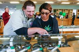 Customers Robert Thompson and Ranita Reed look over a selection of marjiuana products at Harborside Health Center on the first day of recreational marijuana sales in California on Monday, January 1, 2018 in Oakland, California.
