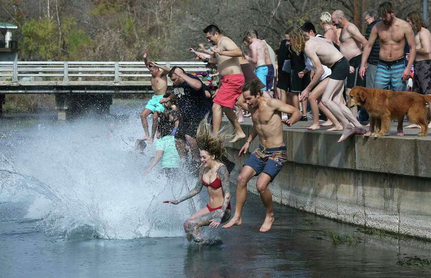 Revelers brave sub freezing temperature and wind chill to jump into the water at Sewell Park during the San Marcos River Plunge on January 1, 2018.