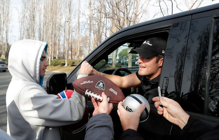 Raiders quarterback Derek Carr signs autographs for fans who waited near the Raiders Headquarters to get autographs and see the players off after the season ended in Alameda, Calif., on Monday, January 1, 2018. Photo: Carlos Avila Gonzalez, The Chronicle