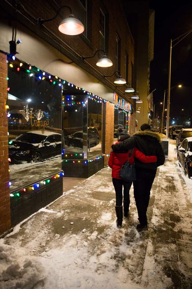 A couple embraces as they walk past Troupe429 in Norwalk, Conn. on Saturday, December 30, 2017. Troupe429, which recently opened on Wall Street, held a reunion party for the now closed LGBTQ Triangles Cafe in Danbury. Photo: Chris Palermo / For Hearst Connecticut Media / Norwalk Hour Freelance
