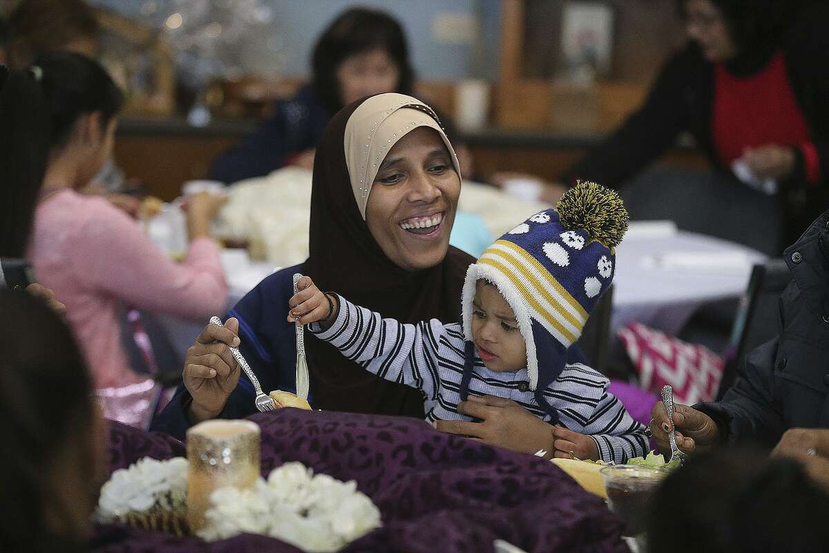 """Abeda Binti Mohammad enjoys lunch with Mohammad Junai Bin Abdul Salam, 2,during the New Year's Day """"Celebration of Hope"""" held by Catholic Charities. Guests were treated to a meal donated by the Olive Garden and served by community volunteers and Catholic Charities executives."""