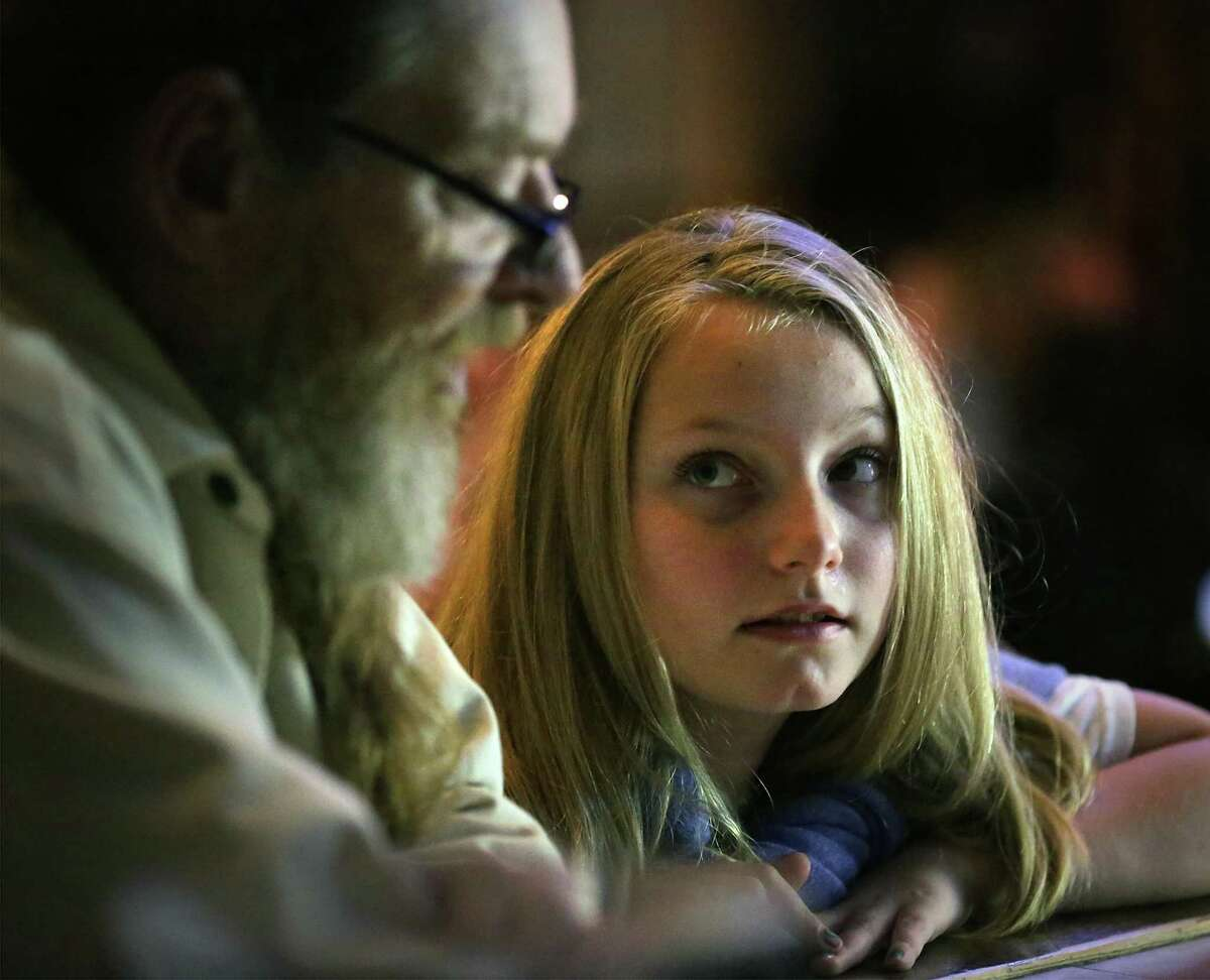 Piper Tilton, 11 years old, talks with her father, local artist Christopher Tilton, before she plays and sings a song she wrote during open mic at The Cove on Dec. 19.