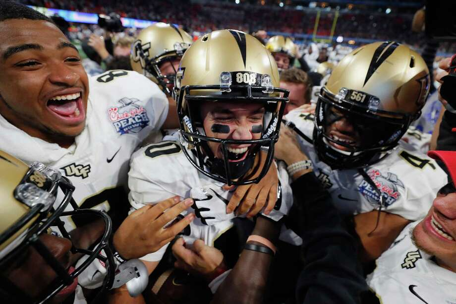 Central Florida quarterback McKenzie Milton is the center of attention after helping lead the 12th-ranked Knights to an upset of No. 7 Auburn in the Chick-fil-A Peach Bowl in Atlanta on Monday. Photo: Kevin C. Cox, Staff / 2018 Getty Images