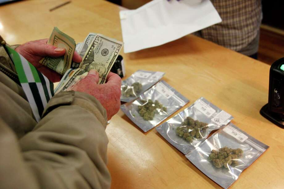 A customer purchases marijuana at Harborside marijuana dispensary, Monday, Jan. 1, 2018, in Oakland, Calif. Starting New Year's Day, recreational marijuana can be sold legally in California. (AP Photo/Mathew Sumner) Photo: Mathew Sumner, FRE / ONLINE_YES