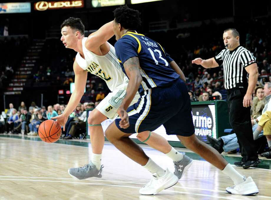 Siena's forward Evan Fisher (32) moves the ball in front of Quinnipiac's forward Chaise Daniels (13) during the first half of an NCAA men's college basketball game on Monday, Jan. 1, 2018, in Albany, N.Y. (Hans Pennink / Special to the Times Union) Photo: Hans Pennink / Hans Pennink