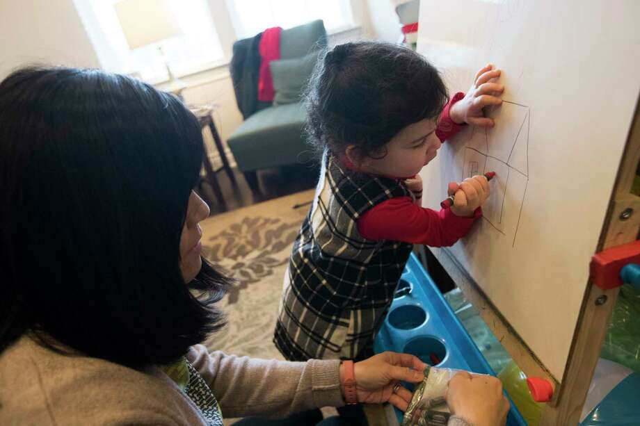 Eliana Yang, 2, makes a drawing representing her bedroom inside her home which got flooded due to the floods caused by Hurricane Harvey. Susan Yang's, left, resolution for the New Year is to return to normalcy in their home. Sunday, Dec. 31, 2017, in Houston. ( Marie D. De Jesus / Houston Chronicle ) Photo: Marie D. De Jesus, Houston Chronicle / © 2017 Houston Chronicle