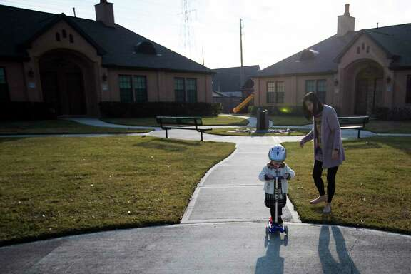 Susan Yang accompanies her daughter to the edge of the community, Sunday, Dec. 31, 2017, in Houston, where they are living temporarily after their home was damaged due to the excess of rain Hurricane Harvey brought to the region. ( Marie D. De Jesus / Houston Chronicle )