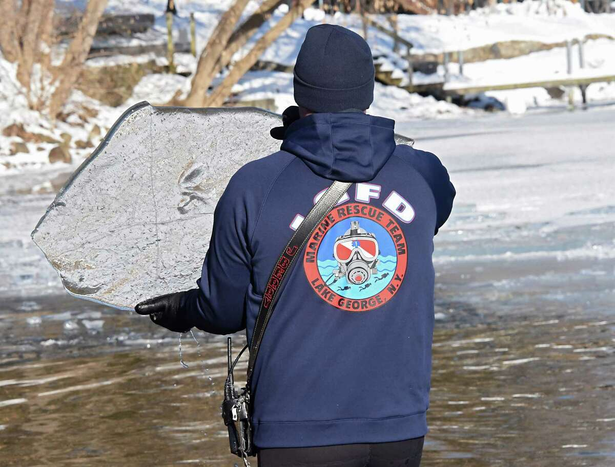 Lake George Fire Department Chief Jason Berry removes a large sheet of ice from the swimming area during the annual Polar Plunge at Shepard Park Beach on Monday, Jan. 1, 2018 in Lake George, N.Y. (Lori Van Buren / Times Union)