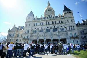 Hundreds of unionized state employees joined together to march outside of the state Capitol building to underscore how potential layoffs will affect Connecticut's quality of life in Hartford, Conn. on Tuesday, March 29, 2016.