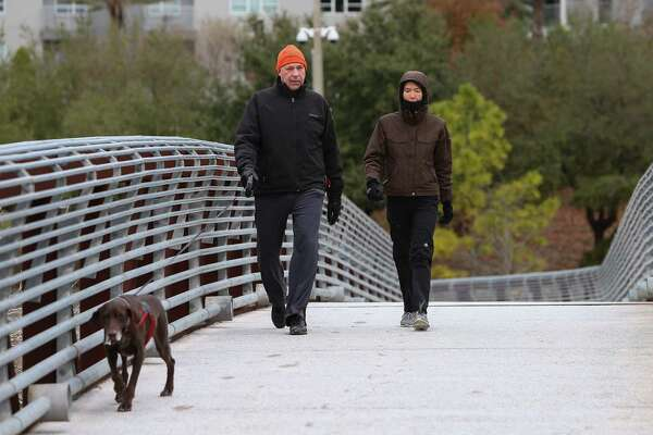 Greg, left, and Emily Kostiuk walk their 10-year old dog Dotty on the Rosemont Pedestrian Bridge Tuesday, Jan. 2, 2018, in Houston. Houstonians woke up to cold weather, with the temperature in the high 20s.
