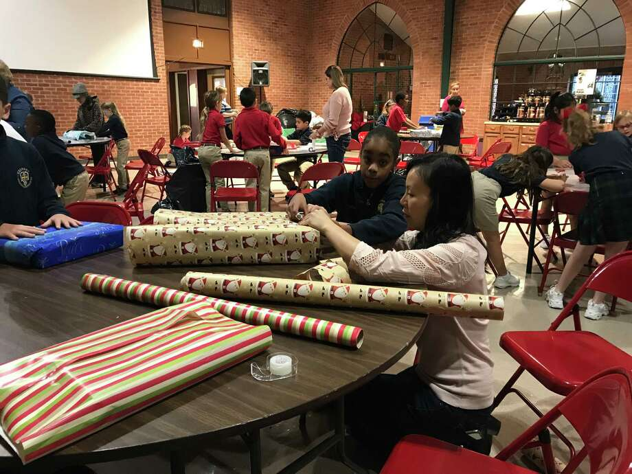 The Richmond Police Department got an assist again this year from the second and fourth grades at Calvary Episcopal Preparatory. They sponsored a toy collection drive, and with contributions from their fellow Crusaders, provided over 140 gifts for children. Students enjoyed wrapping presents to be delivered to the Santa Behind the Badge program which is sponsored through the Richmond PD. Above,  Jamie Lee assists Bailee Debbs with wrapping presents. Photo: Calvary Episcopal Preparatory