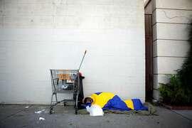 Homeless man sleeps on Octavia Street sidewalk