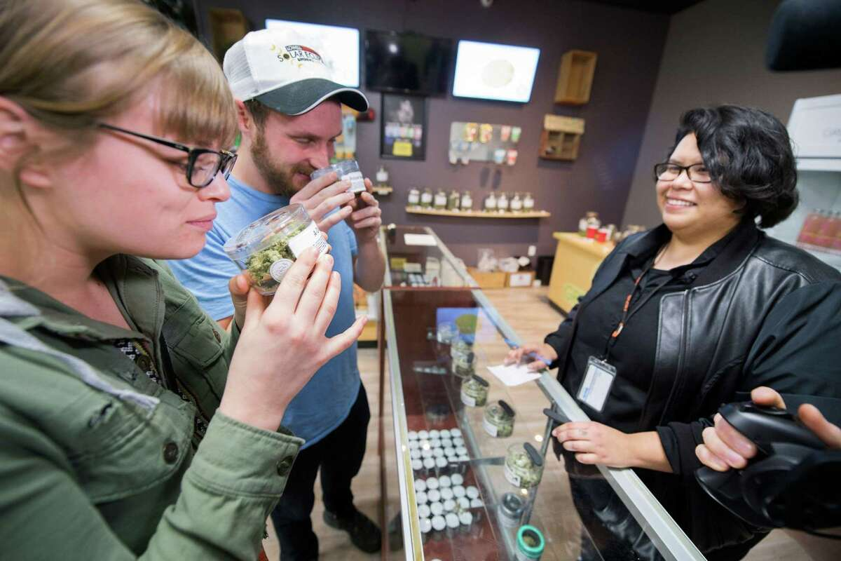 Tourists Laura Torgerson and Ryan Sheehan, visiting from Arizona, smell cannabis buds at the Green Pearl Organics dispensary on the first day of legal recreational marijuana sales in California, January 1, 2018 in Desert Hot Springs, California.