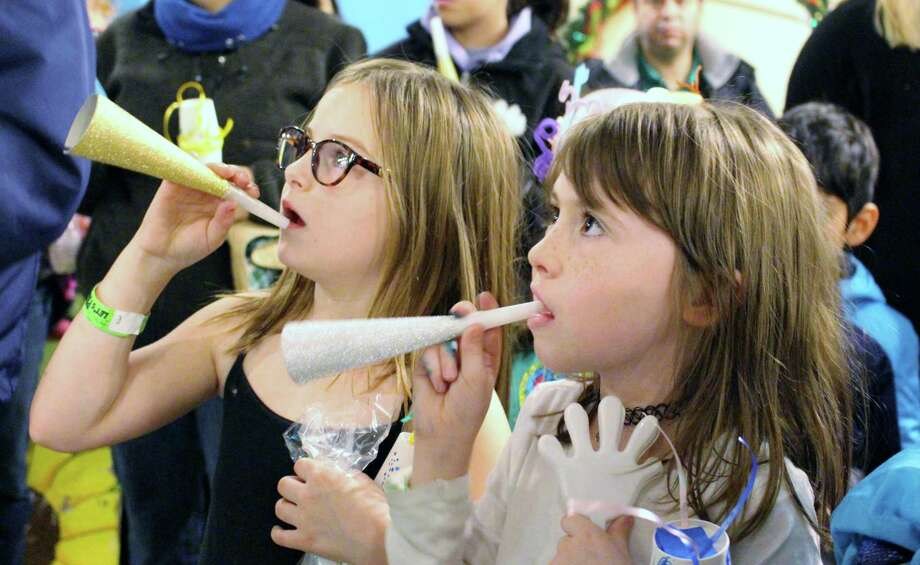 Taylor,8 and Avery,6 eagerly blow their NYE horns moments before the balloon drop at the High Noon Countdown at The Woodlands Children's Museum in Panther Creek on Sunday, Dec. 31. Photo: Michelle Iracheta