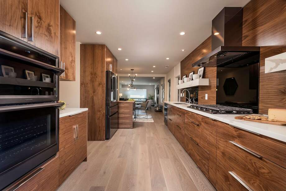 The kitchen hosts a wood floor and integrated cooktop. Photo: Obeo