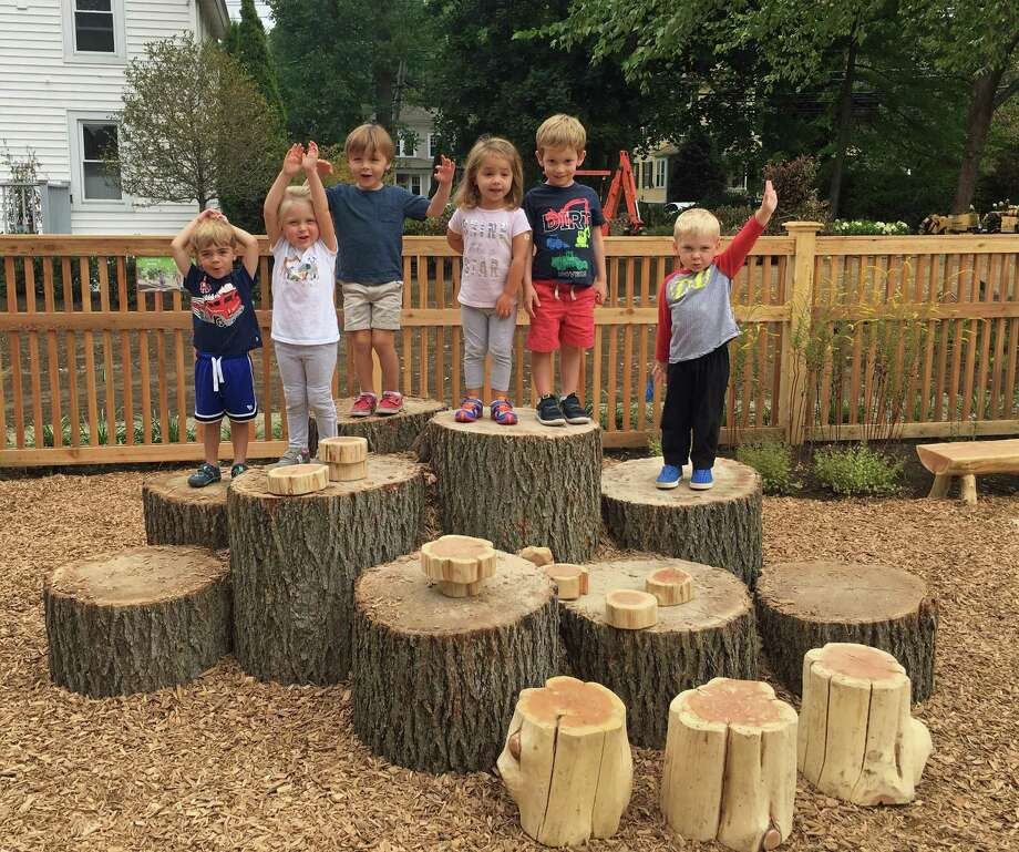 First Church Preschool students William Heizman, Beatrix Evans, Jack Golden, Grace Johnson, Reid Wenitzky, and Indy Woolf, all 3 years old, pose on logs in their school's nature classroom. Photo: Contributed