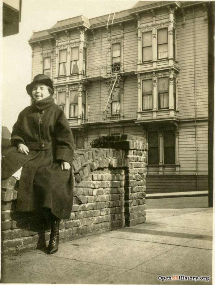 A woman posing against brick wall, with 1192 Haight in the background.Photo courtesy of OpenSFHistory. Photo: OpenSFHistory/Courtesy
