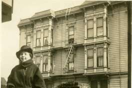 A woman posing against brick wall, with 1192 Haight in the background. Photo courtesy of OpenSFHistory.