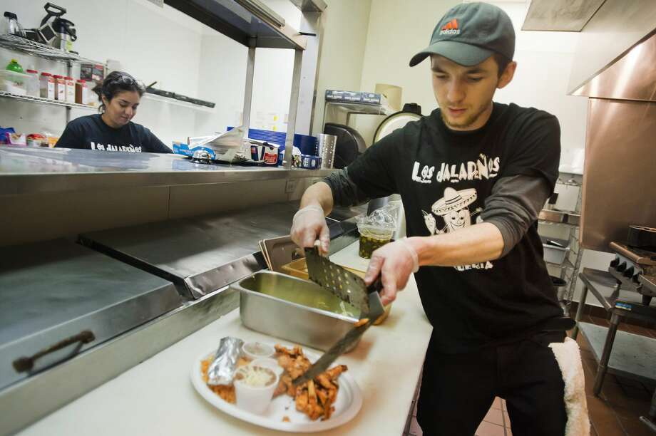 Ryan Chamberlin prepares dishes inside the kitchen of the new Los Jalapeños brick-and-mortar restaurant, which is located at 1900 S. Saginaw Rd., while Mykela Finney prepares to serve customers on Tuesday, Jan. 2, 2018 in Midland. (Katy Kildee/kkildee@mdn.net) Photo: (Katy Kildee/kkildee@mdn.net)