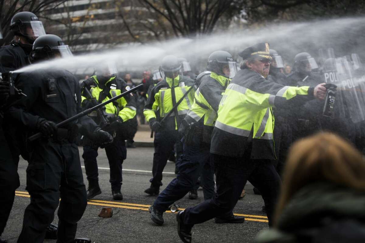 The police pepper sprays into the crowd of protestors and journalists during demonstrations on Inauguration Day, Friday, Jan. 20, 2017, in Washington D.C.