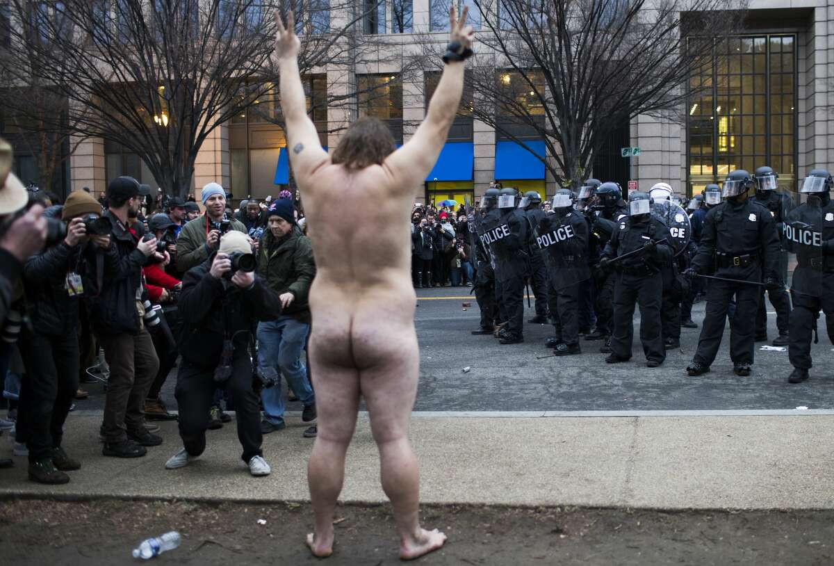 A naked protestor gets naked making peace signs with his fingers after the riot police paper sprayed the crowd during the inauguration of President Donald J. Trump, Friday, Jan. 20, 2017, in Washington D.C.