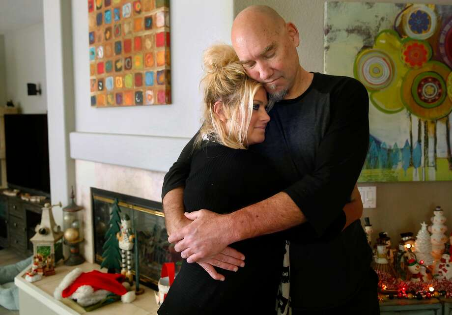 Tom Tolbert, sports radio co-host and former Warriors player, hugs his wife, Lorrie, at their home in Alameda. He had lifesaving heart surgery in August. Photo: Michael Macor, The Chronicle