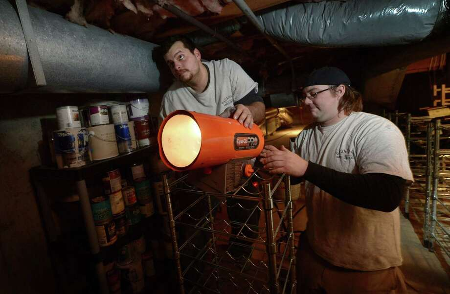Badaracco Plumbing and Heating workers Greg Narowski and Greg Bruder direct a propane heater onto the frozen water pipes of a home Tuesday, January 2, in Westport, Conn. Photo: Erik Trautmann / Hearst Connecticut Media / Norwalk Hour