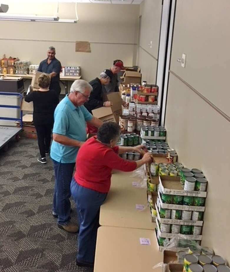 Members of the Conroe Noon Lions Club worked over the holidays to pack 35 Christmas Baskets for area elderly and disable families. Pictured from back to front are Ralph Perez, Lisa Poppell, Bill Miller, Jim Elliott, Richard Parker, and Ladoris Cates. Photo: Submitted Photo