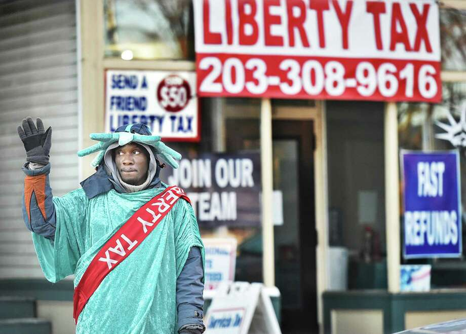 With tax season approaching, New Haven resident Koffi Samuel waves to motorists traveling on State Street in New Haven January 28, 2015. While cybersecurity should be a year-round concern for small business owners, income tax filing season can bring some particular risks, according to the IRS. Photo: Catherine Avalone / / New Haven RegisterThe Middletown Press