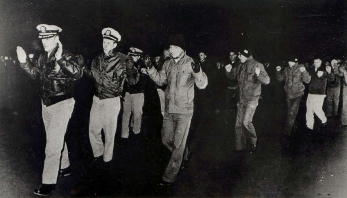 Crew members of the USS Pueblo hold up their hands while in captivity in North Korea in 1968. Many of the crew who served on the vessel, then spent 11 months in captivity in North Korea, want to bring the Pueblo home. It is still being held in North Korea.