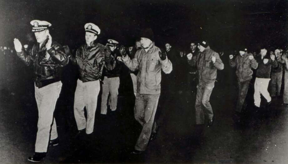 Crew members of the USS Pueblo hold up their hands while in captivity in North Korea in 1968. Many of the crew who served on the vessel, then spent 11 months in captivity in North Korea, want to bring the Pueblo home. It is still being held in North Korea. Photo: Anonymous /Associated Press / US Navy