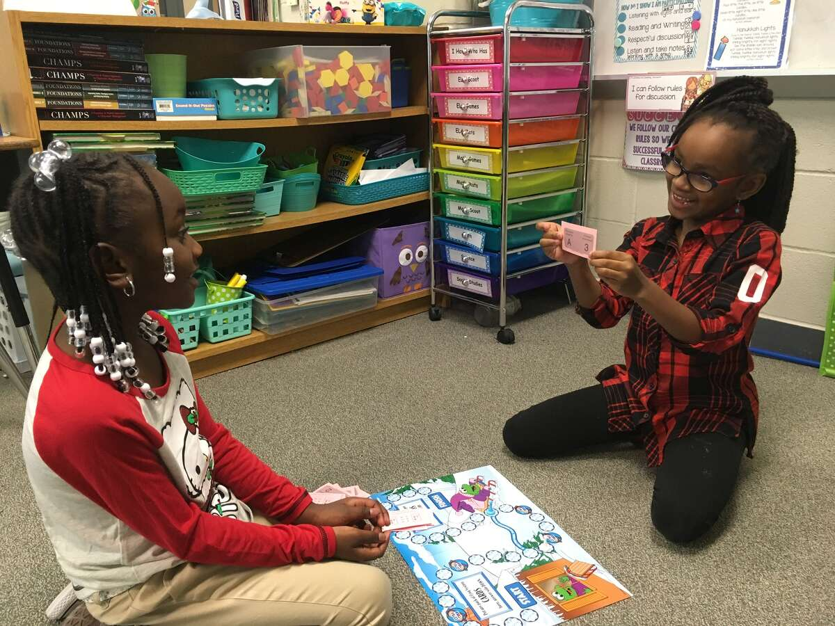 Khloe White and Kylei Labergne play board games in in Kelli Meredith's first grade classroom at Dishman Elementary.