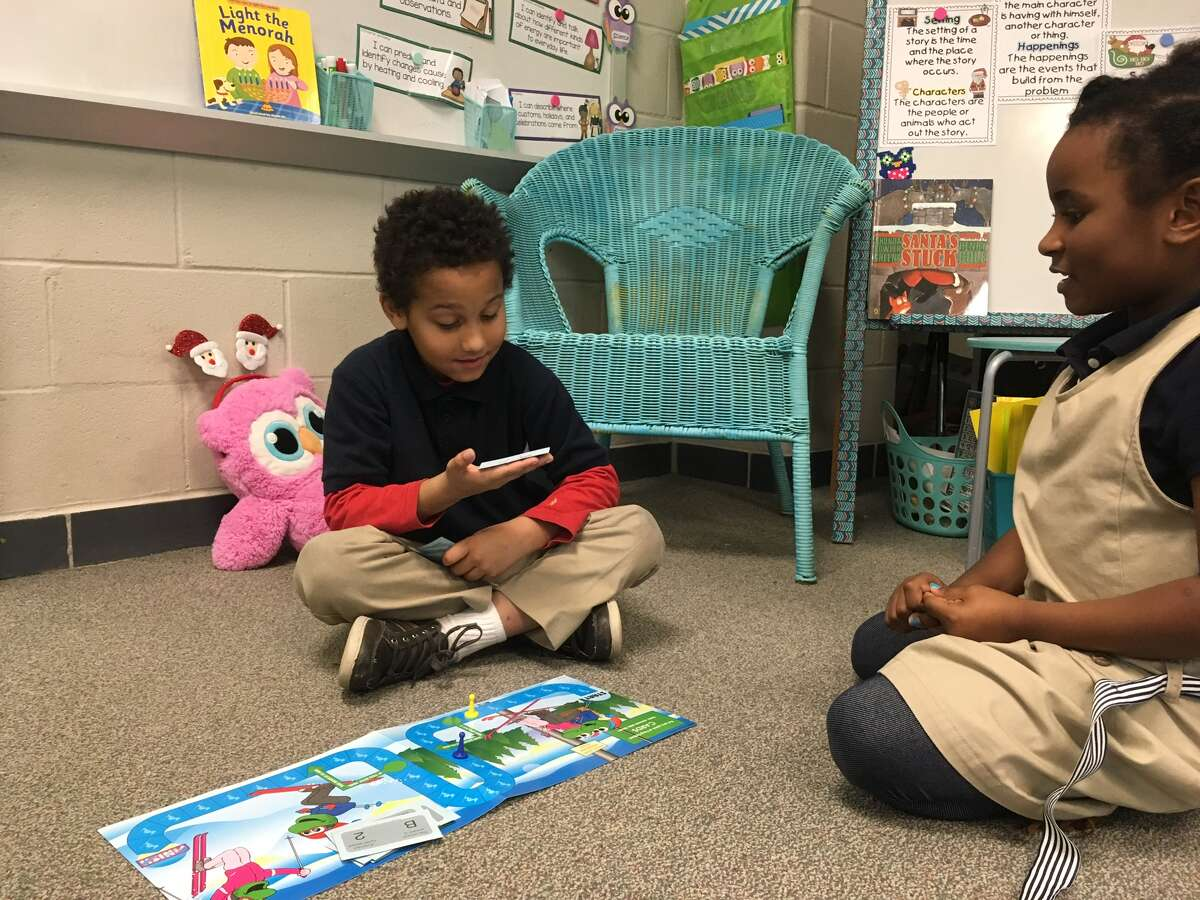 Jordan Jones and Aniyah Brachett play a math board game in Kelli Meredith's first grade class at Dishman Elementary.