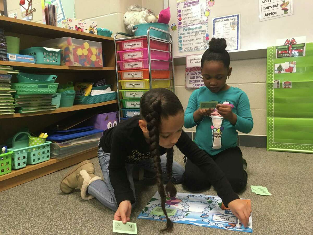 Aeirllynn Hoffpauir and London Ware play a math board game in in Kelli Meredith's first grade classroom at Dishman Elementary.