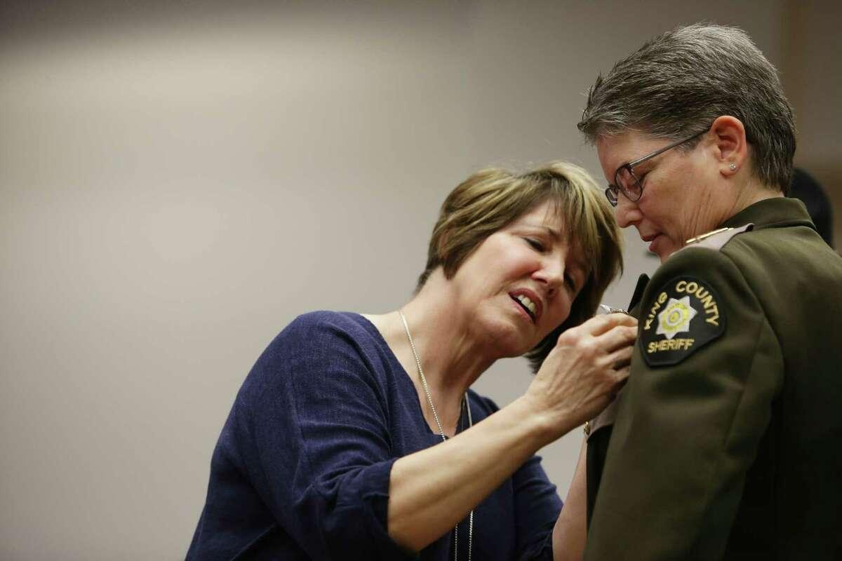 Maureen Warren pins the sheriff's badge on her wife, new King County Sheriff Mitzi Johanknecht, after Johanknecht was sworn in, Tuesday, Jan. 2, 2018 in Seattle. Johanknecht, a veteran of the force, defeated incumbent Sheriff John Urquhart in November.