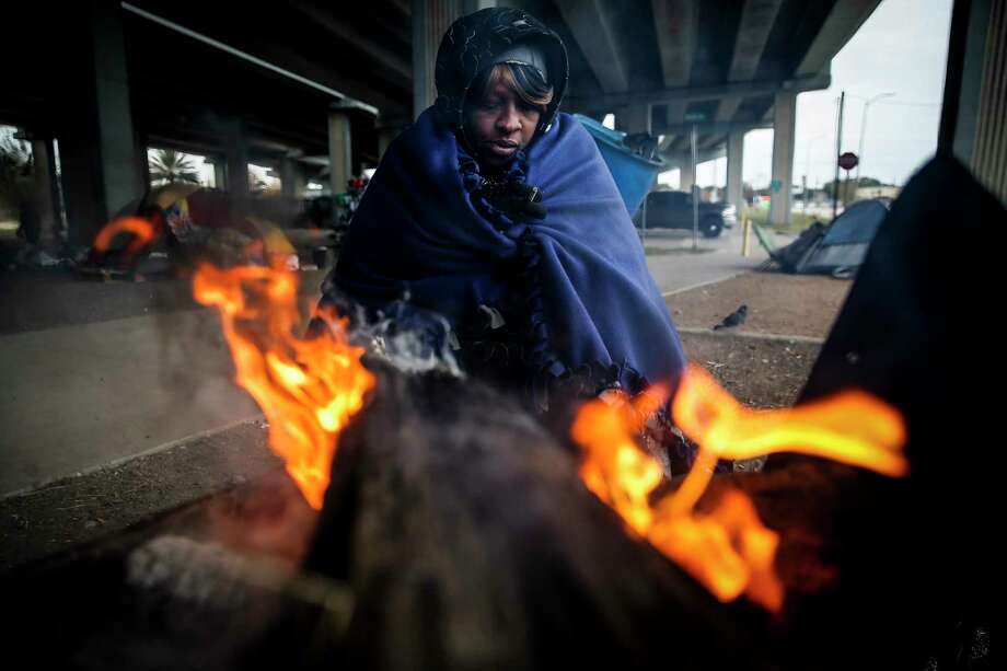 Tony Sampson, who received a blanket from Star of Hope's Love in Action van, tries to warm up by a fire under the Eastex Freeway as temperatures hover in the 30s Tuesday, Jan. 2, 2018 in Houston. ( Michael Ciaglo / Houston Chronicle) Photo: Michael Ciaglo, Houston Chronicle / Michael Ciaglo
