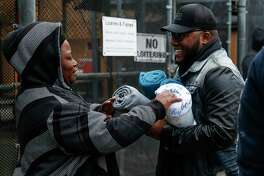Madeline Fredrick, left, picks out a blanket from Star of Hope outreach case manager Kenneth DeVon, right, as he passes out blankets to the homeless as temperatures hover in the 30s Tuesday, Jan. 2, 2018 in Houston. ( Michael Ciaglo / Houston Chronicle)