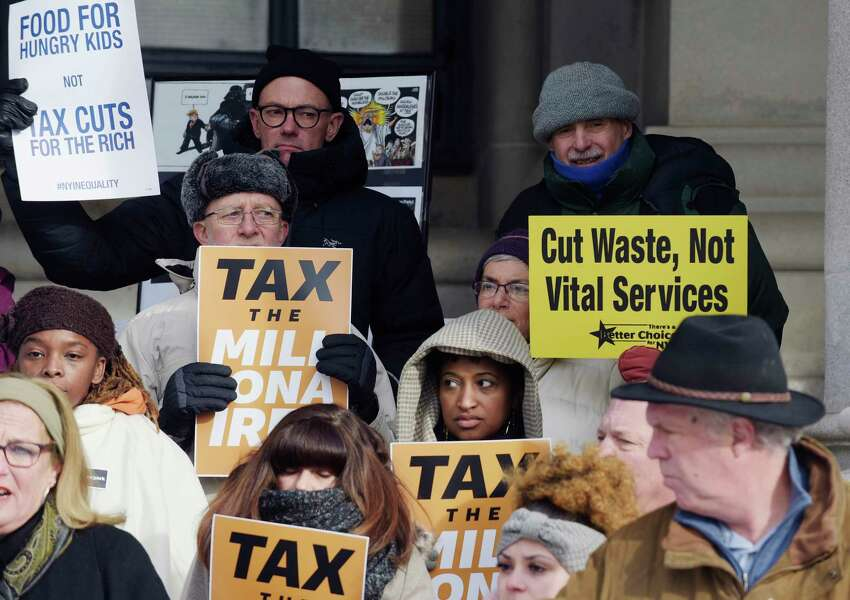People holding various signs take part in the People's State of the State event outside the Capitol on Tuesday, Jan. 2, 2018, in Albany, N.Y. The People's State of the State is held by religious, education and social welfare groups so that they can voice the legislative agenda they feel would be best for the people of New York State. Governor Andrew Cuomo will deliver his State of the State address on Wednesday. (Paul Buckowski / Times Union)