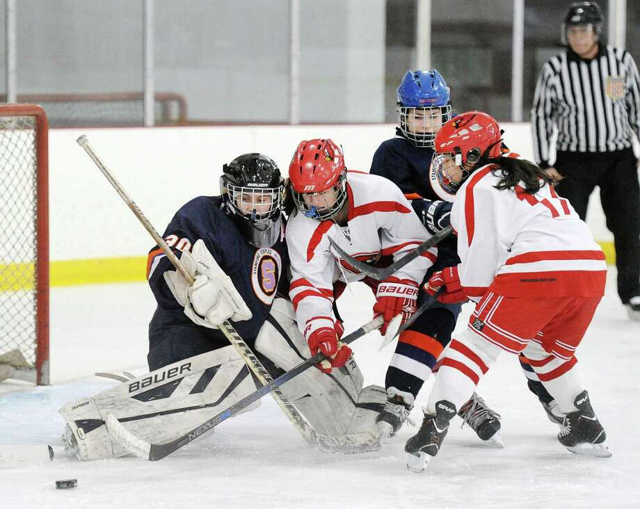 Stamford-Staples-Westhill goalie Mary Leydon, left, makes a stop as she is presurred on the rebound by Greewich players including Emiri Fukuchi (#17), right, during the girls high school ice hockey game between Greenwich High School and Stamford-Staples-Westhill High Schools combined at Hamill Rink in Greenwich, Conn., Tuesday, Jan. 2, 2018. Photo: Bob Luckey Jr. / Hearst Connecticut Media / Greenwich Time