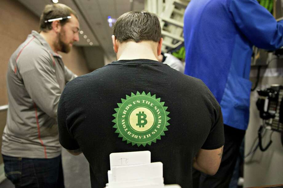 A trader wears a bitcoin shirt while working in the S&P 500 options pit last week at Cboe Global Markets in Chicago. Bitcoin's underlying technology can work against its use by criminals.  Photo: Daniel Acker / © 2017 Bloomberg Finance LP