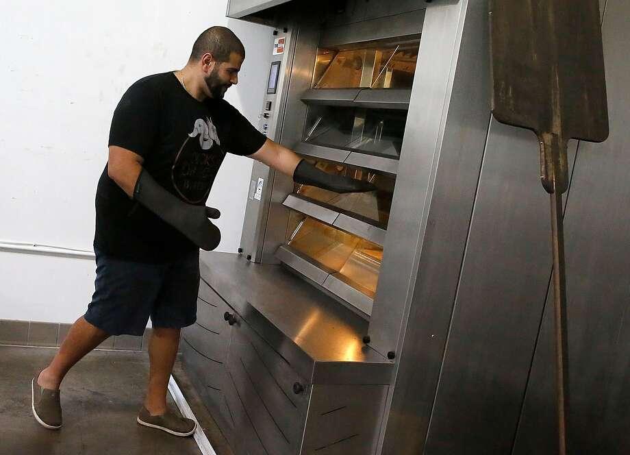 Bakery owner Mina Makram takes gluten-free bread from the oven at Ducks & Dragons bakery in San Carlos. Photo: Liz Hafalia, The Chronicle