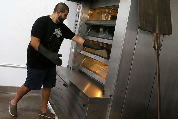 Bakery owner Mina Makram takes gluten-free bread from the oven at Ducks & Dragons bakery on Friday, September 22, 2017, in San Carlos, Calif.