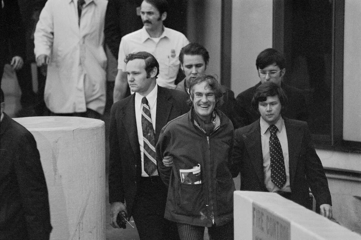 Timothy Leary�laughs as he is escorted by federal officers after arriving in California from London, nearly three years after escaping from prison.
