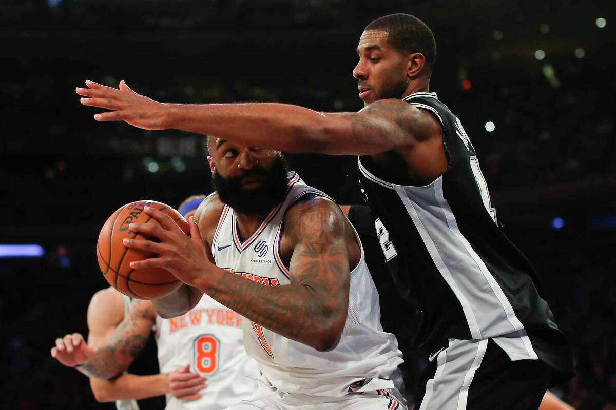 New York Knicks center Kyle O'Quinn (9) looks to shoot against San Antonio Spurs forward LaMarcus Aldridge (12) during the second quarter of an NBA basketball game, Tuesday, Jan. 2, 2018, in New York. (AP Photo/Julie Jacobson)